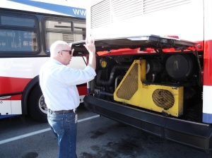 SamTrans Deputy GM, Chuck Harvey, examines the engine compartment of a bus during base inspection.