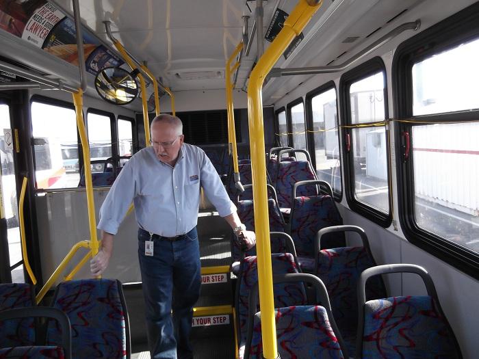SamTrans deputy CEO, Chuck Harvey examines a bus during base inspection.