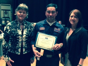 Mechanic Generoso Maranan poses with SamTrans board member Zoe Kersteen-Tucker and a family member.
